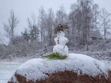 Small snowman on the big stone in snowy and overcast weather