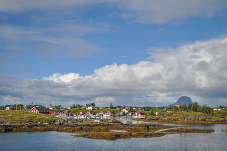 View from ferry to the small fishermen village on island in Helgeland archipelago in the Norwegian sea on sunny summer morning. Silhouette of Lovund island on the background