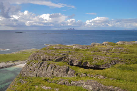View from Lovund hills to the rocky coastline and Lovund archipelago in the Norwegian sea on sunny summer day. White clouds over the blue sea. Silhouette of Træna island on the horizon