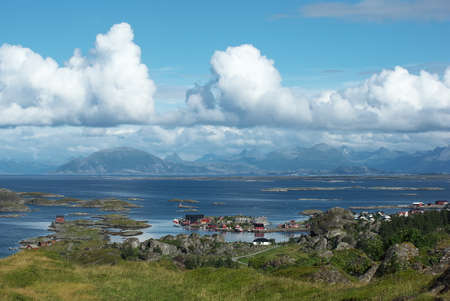 View from Lovund hills to the Helgeland archipelago in the Norwegian sea on sunny summer afternoon. White clouds over the sea
