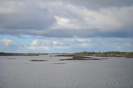 View from ferry to the small rocky islands of Helgeland archipelago in the Norwegian sea on sunny summer morning. White clouds over the blue sea