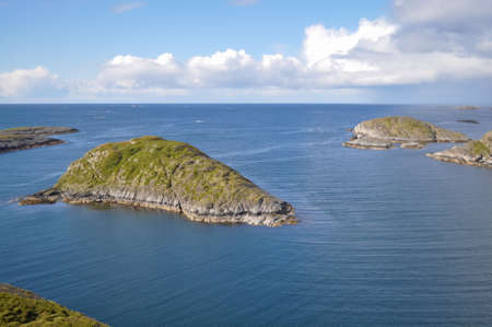View from Lovund hills to the rocky coastline and the small green rocky islands of Lovund archipelago in the Norwegian sea on sunny summer morning. White clouds over the blue sea.