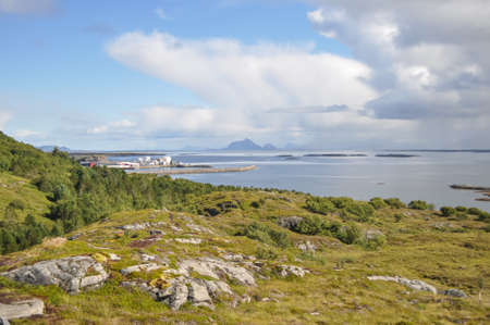 View from Lovund hills to the rocky coastline of Lovundf and Lovund harbor on sunny summer morning. White clouds over the blue sea. Donna island on the horizon. Banco de Imagens