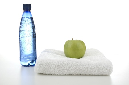 A bottle of water and a towel with an apple on top of it Stock Photo - 9692072