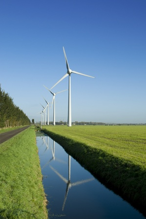 Several windturbines in a green field and reflection in the water