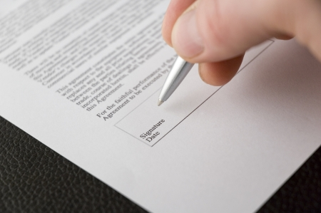 signing contract: A hand signing a contract