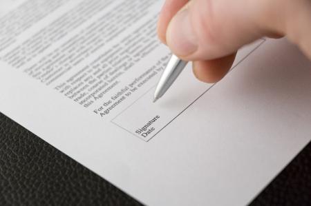 firmando: Una mano en la firma de un contrato Foto de archivo