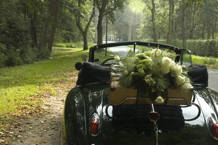 A classic wedding car and a bouquet of flowers