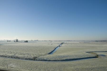 A windmill in a dutch winter landscape photo