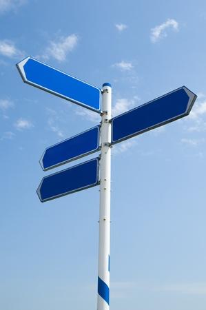 青い曇り空を背景の空の道路標識 写真素材