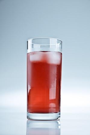 赤いレモネードや氷のキューブのガラス
