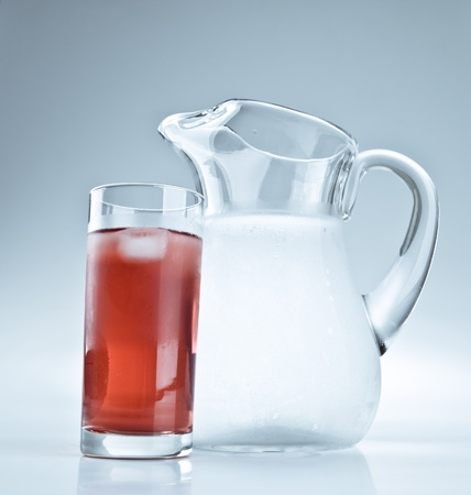 Water pitcher and a glass of red lemonade photo