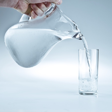 Water pitcher pouring a glass of fresh water photo