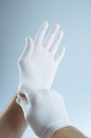 safety gloves: Doctor putting on protective gloves Stock Photo
