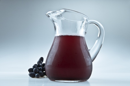 A pitcher of lemonade and some grapes Stock Photo