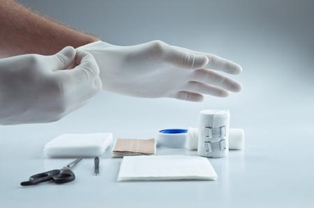primeros auxilios: Suministros médicos de primeros auxilios y un médico de ponerse los guantes de protección Foto de archivo