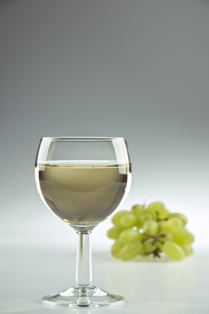 poured: Glass of white wine and some grapes Stock Photo