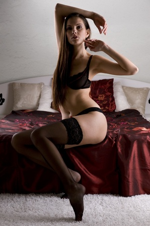 Beautiful brunette posing in lingerie on a bed Stock Photo