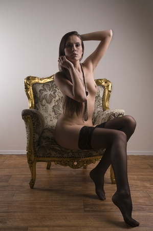 Beautiful brunette posing nude sitting in a chair photo