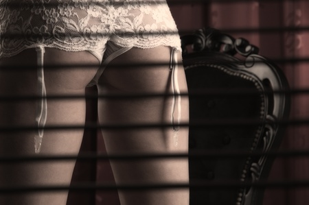 Gorgeous female standing in lingerie behind blinds Stock Photo