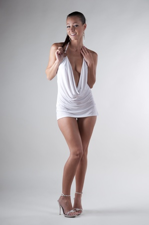 Brunette standing in a white dress photo