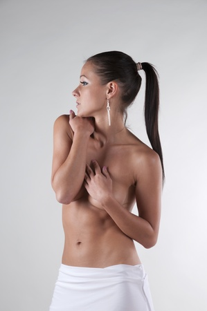 Beautiful brunette with ponytail posing topless