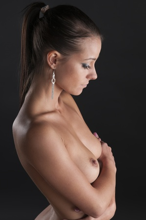 Beautiful female posing nude on a black background
