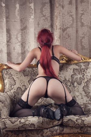 beautiful redhead wearing lingerie and high heels on a couch