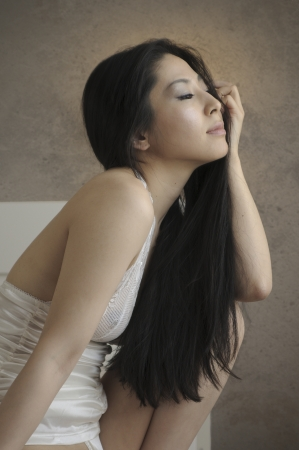 Beautiful asian woman sitting on her bed