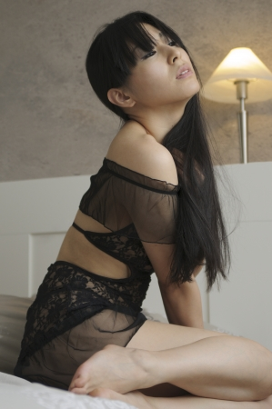 Beautiful asian woman sitting on her bed Stock Photo - 14531997