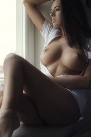 young nude girl: Sch�ne Br�nette posiert nackt vor der Fenster