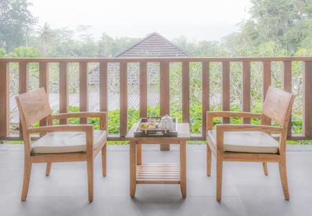 wooden garden furniture in garden with wooden chair and table. Standard-Bild