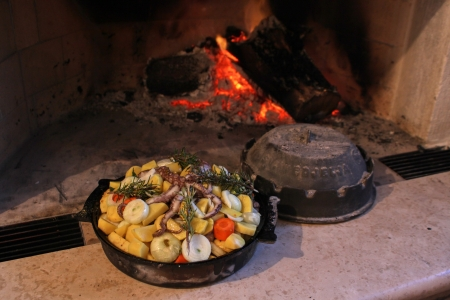 fireplaces: Octopus with potatoes in traditional baking lid at fireplace - typical Croatian food  Stock Photo