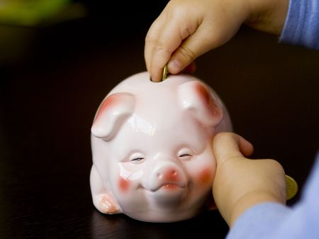 A babys hand dropping a coin into a piggy bank.