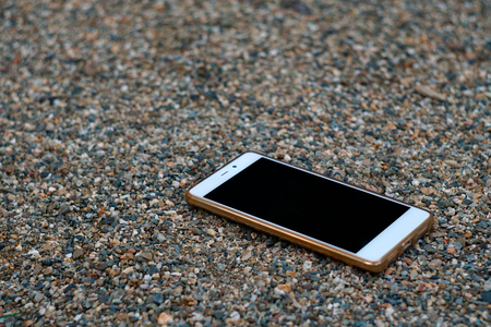 A smartphone with unbroken screen lies on the ground