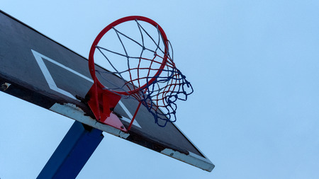 Basketball shabby backboard with a red basketball hoop in cloudy weather