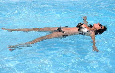 brunette girl in bikini bathing in a pool of blue water on a sunny summer day Stockfoto