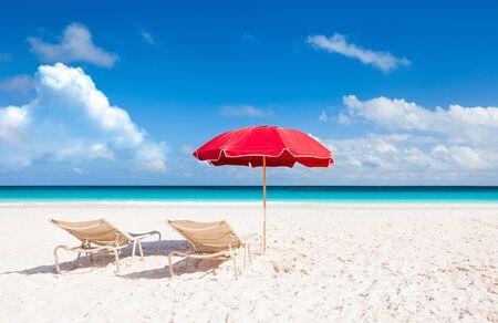 Sommerstrandszene mit rotem Regenschirm Standard-Bild