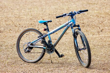A generic bicycle on stand in an open field
