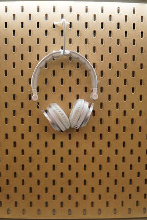 White headphones on wooden pegboard background with various concept colour Stock Photo