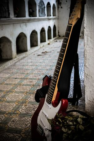 Red guitar in wall of cemetery