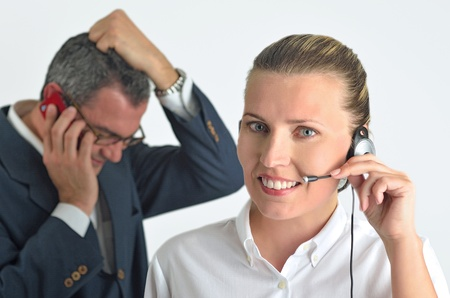 Beautiful business woman with headset and talking to a angry businessman photo
