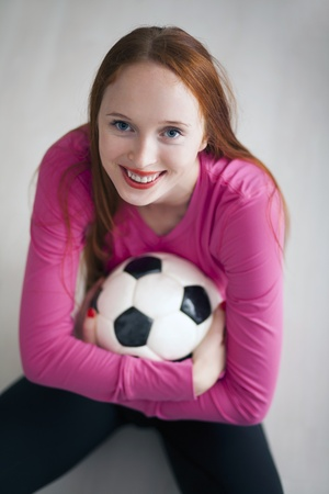Beautiful blond girl holding a soccer ball and sitting on floor Stock Photo - 13501215