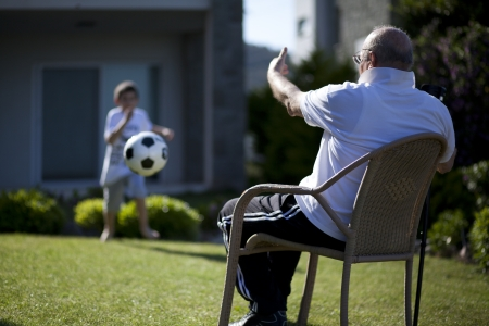Old man with walking stick sitting on chair and teaching football playing to his adorable grandson photo