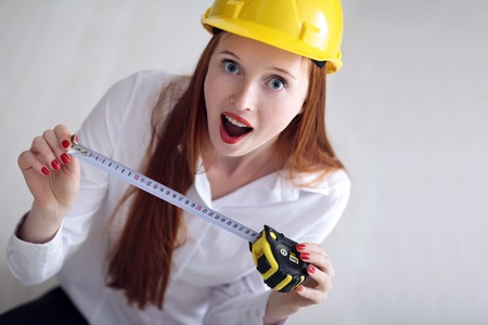 Long haired woman with yellow helmet holding a tape measure photo