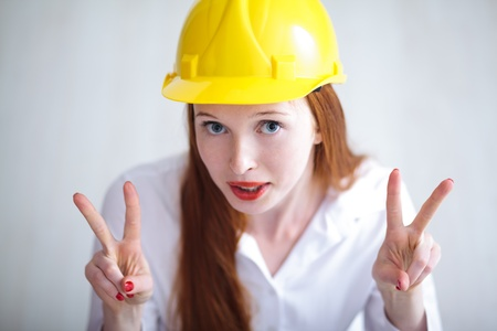 Long haired happy girl with yellow helmet showing the v sign photo