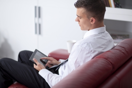 Happy young businessman holding and touching a digital tablet and sitting on couch Stock Photo - 14473320