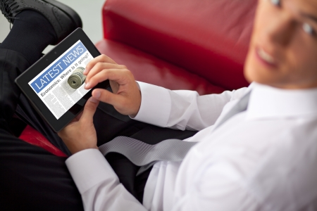 Businessman finger touching screen of a digital tablet and sitting on couch photo