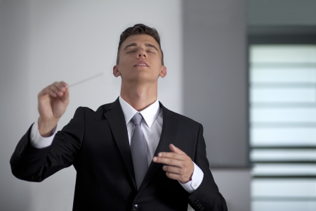Businessman conducting his work and business with his baton photo