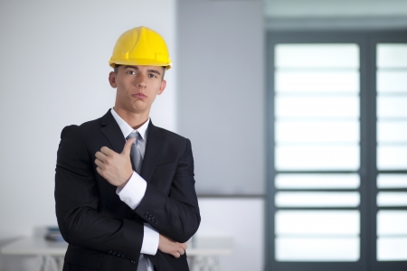 Young businessman wearing a safety hat and hand gesturing thumbs up success sign photo
